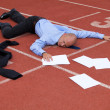 View of a businessman lying on a race track - Stock Photo