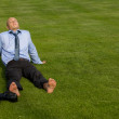 Businessman relaxing in park - Stock Photo
