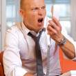 Businessman shouting on landline phone -  