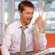 Businessman shouting on landline phone - Stock Photo