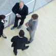 Businessmen and businesswoman standing together by railing -  