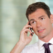 Portrait of businessman using mobile phone at office - Stock Photo