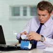 Stock Photo: Businessmsearching for card by laptop in office