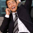 Businessman using telephone in office, smiling — Stock Photo #3829324