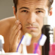 Reflection of young man in mirror applying shaving cream — Stock Photo