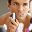 Reflection of young man in mirror shaving with electric shaver — Stock Photo