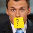 Portrait of businessman in office with question mark written on adhesive note stuck to his mouth — Stock Photo