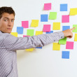 Portrait of businessman pointing at wall of sticky notes — Stock Photo