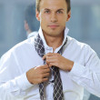 Portrait of businessman tying tie — Stock Photo