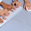 Hands typing on computer keyboard, elevated view — Foto Stock