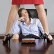Royalty-Free Stock Photo: Businesswoman standing on table in front of businesswoman at office