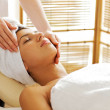 Young woman receiving facial massage, eyes closed — Stock Photo