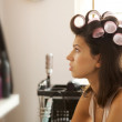 Stock Photo: Young woman with hair curlers