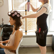 Stock Photo: Female hairdresser spraying hairspray in customer's hair