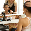 Female customer sitting in front of dressing table while beautician holding — Stock Photo