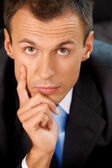 Portrait of businessman contemplating in office with hand on chin — Stock Photo