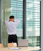 Rear view of businessman standing in office with hands behind head — Stock Photo