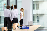 Business team looking through window at office — Stock Photo