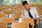 Znudzony biznesmen siedzi w sali konferencyjnej — Zdjęcie stockowe