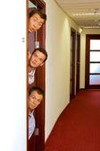 Portrait of businessmen peeking out of door — Stok fotoğraf