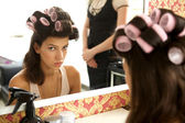 Portrait of young woman with hair curlers — Stock Photo