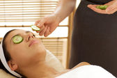Young woman lying on massage table with cucumber slice being placed over eye — Stock Photo