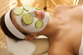 Young woman lying down on massage table with cucumbers on eyes and face — Stock Photo