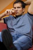 портрет молодого человека пить виски в гостиничном номере — Стоковое фото