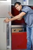 портрет молодого человека открытия двери холодильник — Стоковое фото