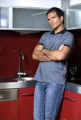 молодой человек стоя на кухне со скрещенными руками — Стоковое фото