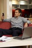 Jovem, segurando o telefone celular, laptop, mantida-se na tabela — Foto Stock