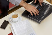 человек, используя ноутбук с чаем, газеты и мобильный телефон держал на столе — Стоковое фото
