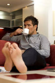 Young man drinking tea, sitting in sofa — Stock Photo