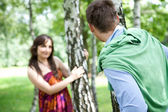Young couple standing in park by tree trunk — Stock Photo