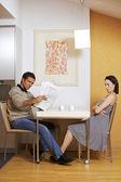 žena na muže čtení novin u stolu se snídaní — Stock fotografie