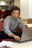 Portrait of young man on the phone, using laptop — Stock Photo