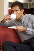 Portrait of young man drinking tea, sitting in sofa — Stock Photo