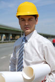 Portrait of architect in hardhat holding blueprint at construction site — Stock Photo