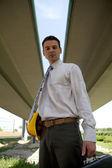 Portrait of architect holding hardhat and laptop bag — Stockfoto