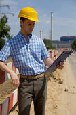 Portrait of architect looking at clipboard — Stock Photo