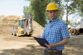 Architect holding clipboard at construction site, bulldozer in background — Stock Photo