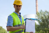 Portrait of architect holding clipboard and showing thumbs up sign — Stock Photo