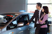 Car salesman and female customer looking at new car — Stockfoto