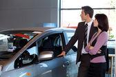 Cliente de vendedor e fêmea de carro olhando carro novo — Foto Stock