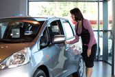 Young woman looking at new car — Stock Photo