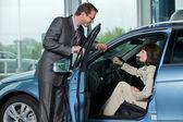 汽车销售人员向客户解释汽车特点 — 图库照片