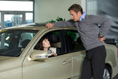 Young woman sitting in new car while young man standing outside car — Stock Photo