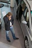 Young man examining new car at showroom — Stock Photo