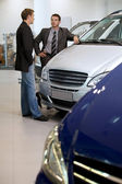 Car salesperson talking with customer — Stock Photo