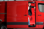 Young man looking through van door, portrait — Stock Photo